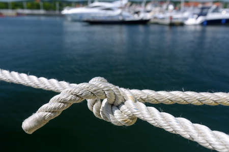 Yachting and marine concept. Close-up of a sea knot on a blurred background of boats moored in the harbor Stock fotó