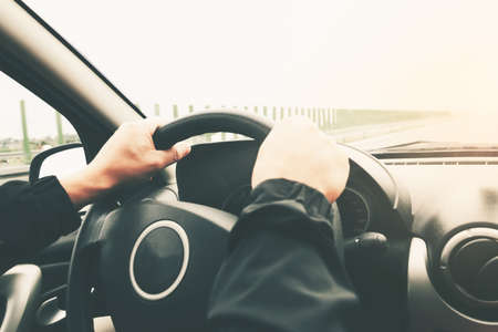 Close-up on male hands on the steering wheel of a car on a blurred background of the highway. Image with modified tones, vintage effect.