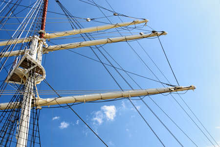 Details of the masts and rigging of the sailing ship against the blue sky in close-up