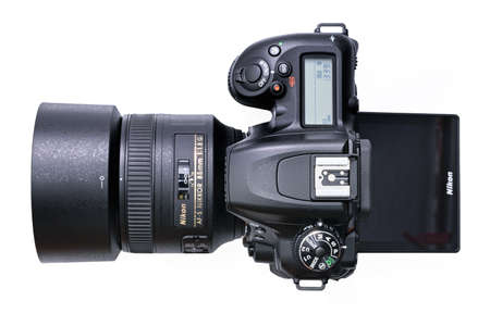 Krakow, Poland - April 09, 2021: Top view of a new Nikon D7500 DSLR camera with Nikkor 85mm F1,8 lens on a white background. Nikon is a famous Japanese corporation specializing in optics and imaging products. Stock fotó - 167709626