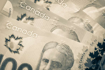 Currency of Canada. Close-up of some Canadian dollar banknotes. Image modified in vintage style