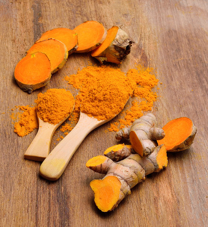 curcumin: fresh turmeric roots in wooden spoon on wooden table