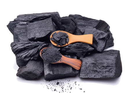 Natural wood charcoal and charcoal powder on wooden spoon isolate on white background