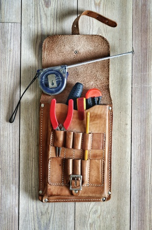 tool bag: leather tool bag with handtools. wooden plank background Stock Photo