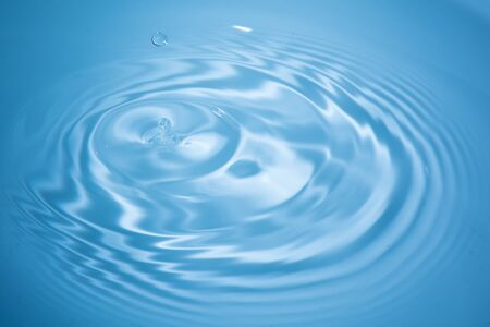Drop of water falls into blue water