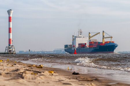 A container ship on the Elbe in front of the Blankenese lighthouse Standard-Bild