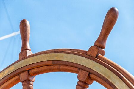 The wooden steering wheel on a sailing ship