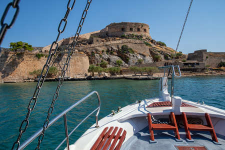 Boat in front of the fortress and leper colony of Spinalonga