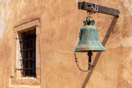 A historical bell in front of a Mediterranean wall 版權商用圖片