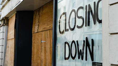Closing down sign in a boarded-up shop window