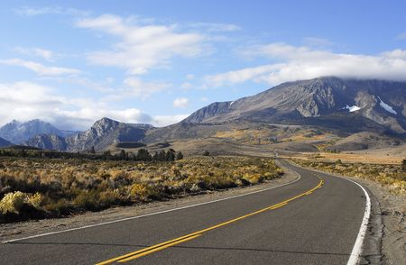 road in high desert leading to fall mountain scenery Stock Photo - 590124