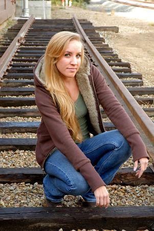 woman kneeling: young woman kneeling between train tracks at railroad museum Stock Photo