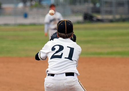 baseball player on first base ready to catch ball