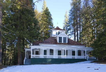 treed: victorian style cabin in woods in winter. Cabin is part of a resort hotel complex