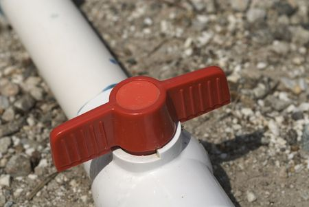 red valve on PVC irrigation pipe in closed position Imagens