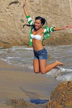 beautiful hawaiian woman jumping off rock on beach Banco de Imagens