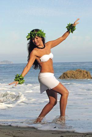 美しい若いポリネシア女性はビーチでの伝統的な踊りを実行します。