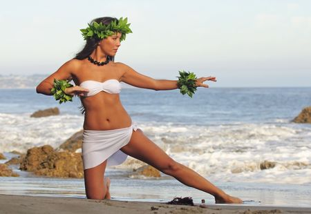 beautiful young Polynesian woman performing traditional dance on beach photo