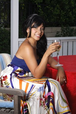 beautiful young woman in colorful dress sitting in gazebo holding a glass of wine Banco de Imagens