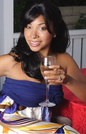 beautiful young woman in coloful dress sitting in gazebo holding a glass of wine