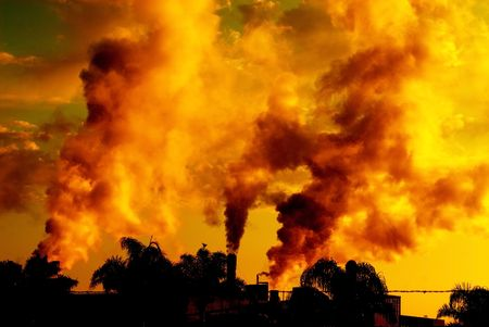 industrial plant releasing polluting smoke photographed at sunset