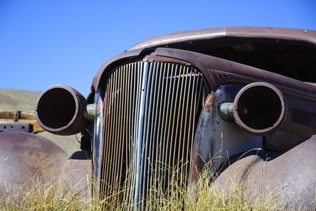 rusted remnants of old car in old west ghost town photo