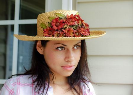 young woman outdoors wearing a straw hat