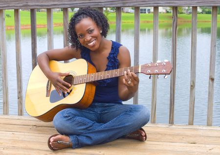 pretty african-american woman with acoustic guitar