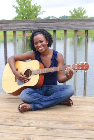 pretty african-american with guitar sitting on dock photo