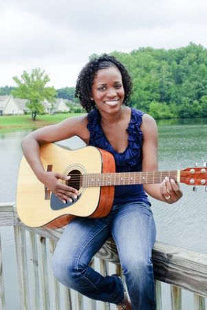 beautiful young black woman with guitar by lake