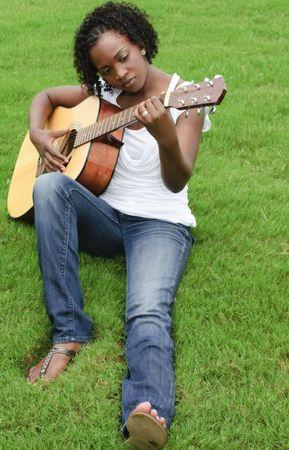 pretty black girl sitting on lawn playing guitar
