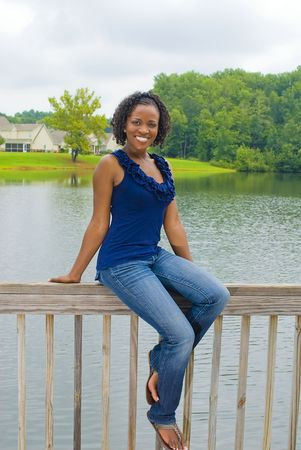 beautiful african-american woman sitting on railing by lake Banco de Imagens