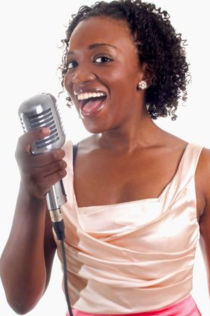 young, pretty african-american woman with microphone performing a song Banco de Imagens