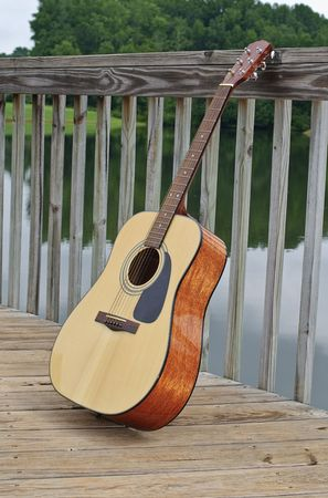acoustid guitar leaning on railing by lake photo