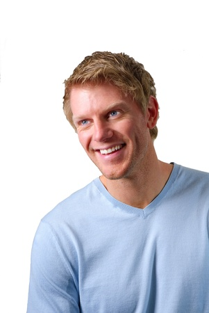 portrait of a blond smiling young man wearing blue sweater