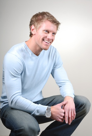 smiling young man posing in squatting pose photo