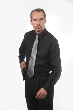 Agent wearing black shirt drawing gun from holster