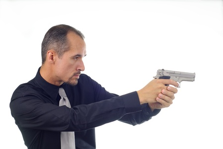 man holding gun: man in black shirt aiming semi-automatic pistol Stock Photo