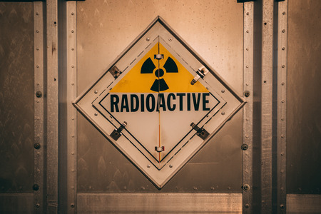 Radioactive yellow danger sign on metal wall Stockfoto
