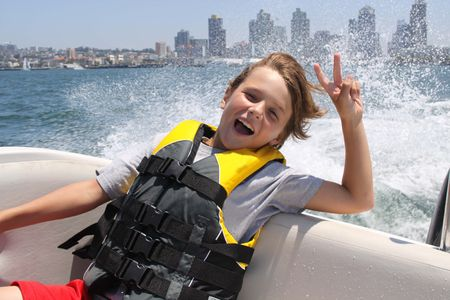 safety vest: Boy in a boat holding up a peace sign