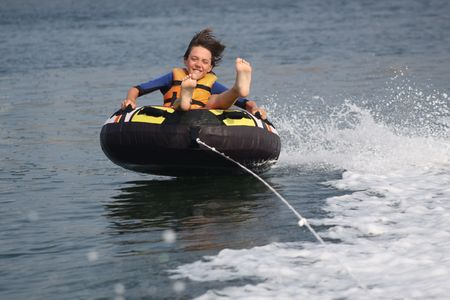 tubing: Boy on inner tube pulled by a boat