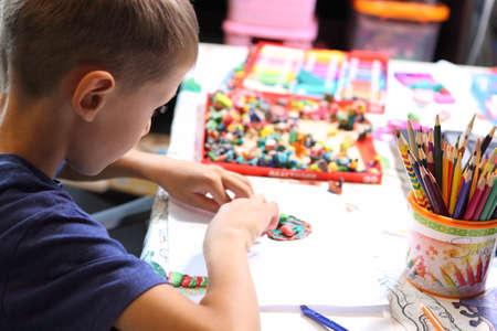 Children's creativity. The boy sculpts from plasticine. Closeup