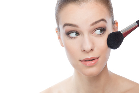 Woman applying make-up  with a brush photo