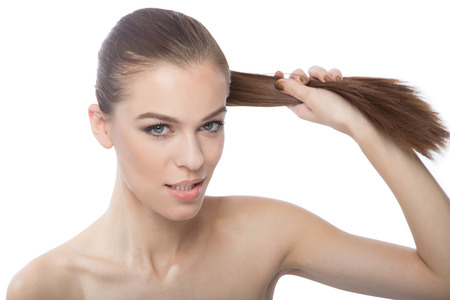 Beautiful woman pulling her long straight hair,over white backgroung Stock Photo