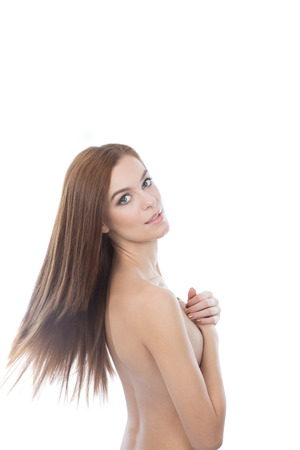 Caucasian red hair woman covering her breats. White background, copyspace. Beautiful long healthy looking hair. photo