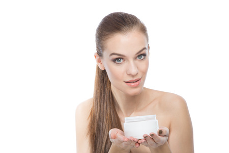 Fashion model holding a moisturizer or treatment, looking at the camera ,over a white background photo