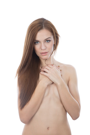 A portrait of a naked woman covering her breast with arms, looking at the camera. Isolated on white background. photo