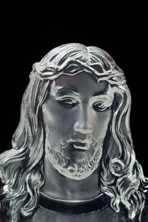 A black and white closeup of a crystal sculpture of Jesus