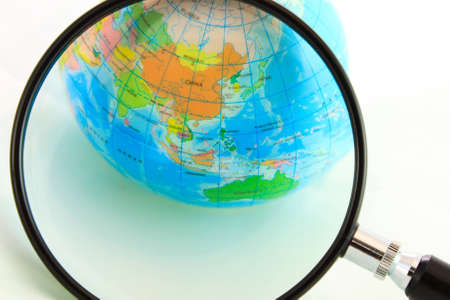 A magnifying glass view of a small colored globe isolated on a white background