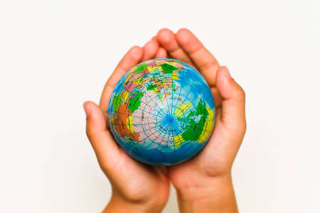 A childs hand holding up a small colored world globe on an isolated background photo
